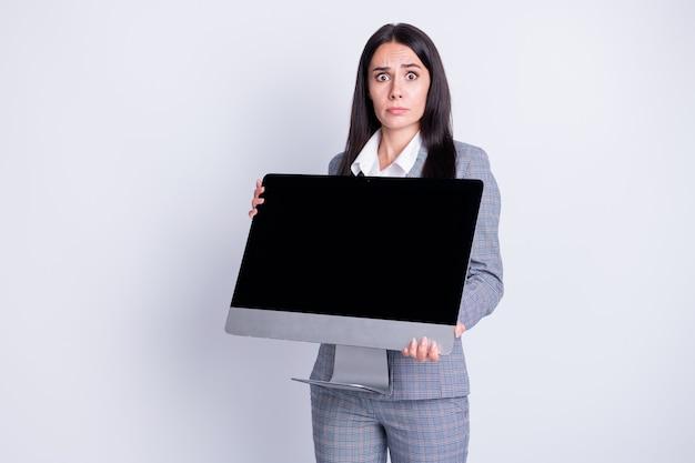 Foto einer attraktiven entlassenen traurigen verängstigten dame, die einen großen computerbildschirm hält, der digitale geräte bis spät in die nacht stiehlt, bürogebäude braucht geld, formelle kleidung, karierter anzug, isoliert grauer farbhintergrund