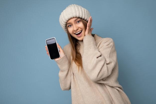 Foto einer attraktiven erstaunten jungen blonden frau, die einen stylischen beige pullover und einen beige gestrickten winter trägt