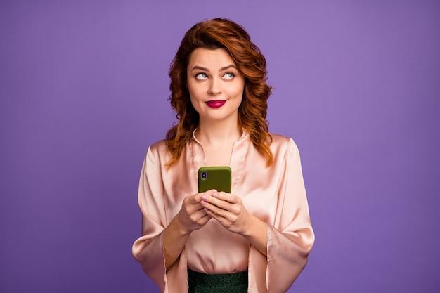 Foto einer attraktiven hübschen dame, die das telefon mit der seite nach oben in den leeren raum hält