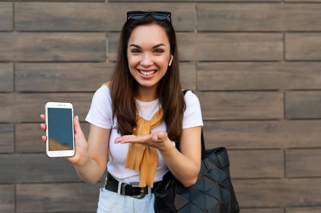 Foto einer attraktiven lächelnden, glücklichen jungen frau, die freizeitkleidung trägt, die auf der straße steht und ein mobiltelefon mit blick auf die kamera hält und zeigt