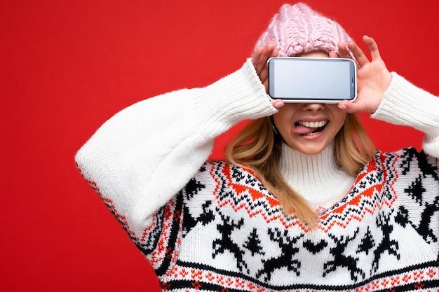 Foto einer attraktiven lächelnden jungen blonden frau mit warmer strickmütze und warmem winterpullover, die isoliert auf rotem hintergrund steht und smartphone mit leerem bildschirm für ausschnitt zeigt und zunge zeigt