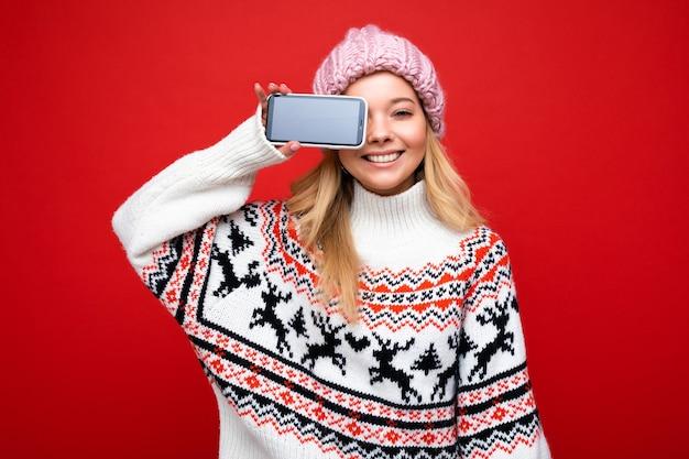 Foto einer attraktiven lächelnden jungen blonden frau mit warmer strickmütze und warmem winterpullover