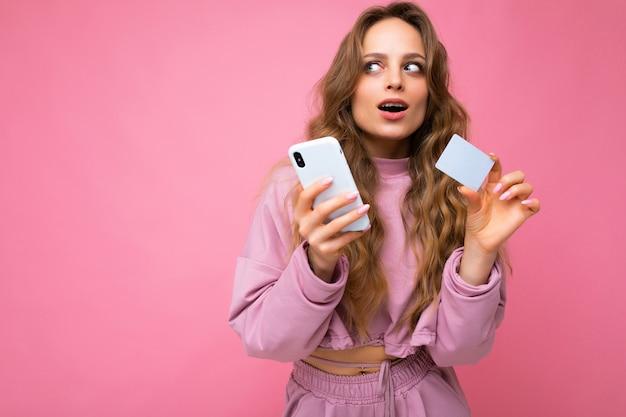 Foto einer attraktiven, nachdenklichen jungen blonden, lockigen frau mit offenem mund, die rosafarbene kleidung trägt, einzeln auf rosafarbenem hintergrund mit mobiltelefon, die zahlung mit kreditkarte vornimmt und zur seite schaut