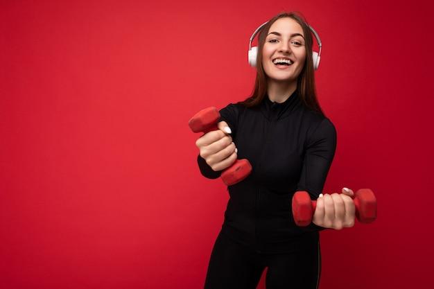 Foto einer attraktiven, positiv lächelnden jungen brünetten frau, die schwarze sportkleidung trägt, isoliert auf