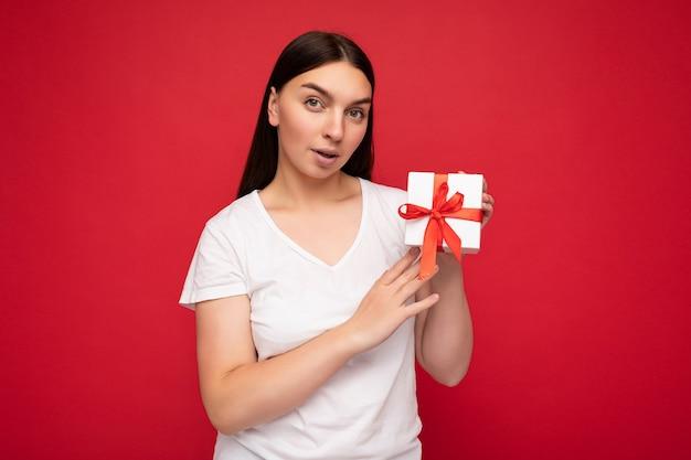 Foto einer attraktiven, positiv überraschten jungen brunet-frau, die über einer roten hintergrundwand isoliert ist und ein weißes t-shirt für ein modell trägt, das weiße geschenkbox mit rotem band hält und in die kamera schaut