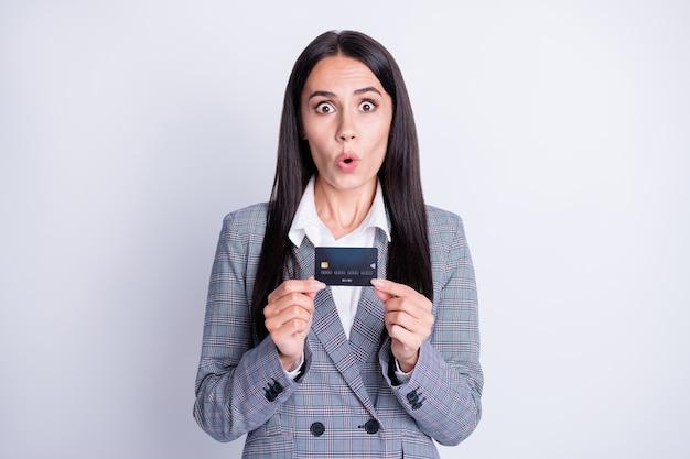 Foto einer attraktiven, schockierten, sprachlosen bankierin mit plastik-debit-kreditkarte neue verrückte große kommissionsbanking-online-überweisung einzelhandelsservice formelle kleidung isoliert grauer farbhintergrund