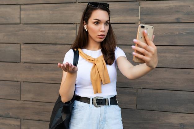 Foto einer attraktiven, schockierten, überraschten jungen frau in freizeitkleidung, die auf der straße steht und auf dem handy spricht und auf das smartphone schaut.