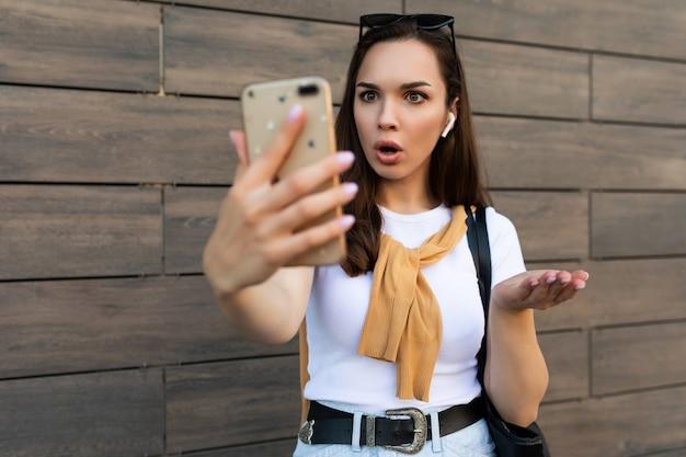Foto einer attraktiven, schockierten, überraschten jungen frau in freizeitkleidung, die auf der straße steht und auf dem handy spricht und auf das smartphone schaut