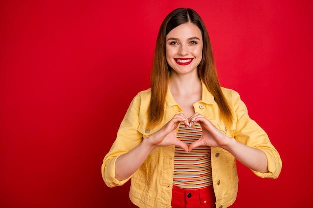 Foto einer attraktiven überglücklichen dame, die gute laune hält, die arme zusammenhält, so dass die finger herzfigur herzgefühle ausdrücken, lässige gelbe blazerjacke tragen, isoliert leuchtend roter farbhintergrund