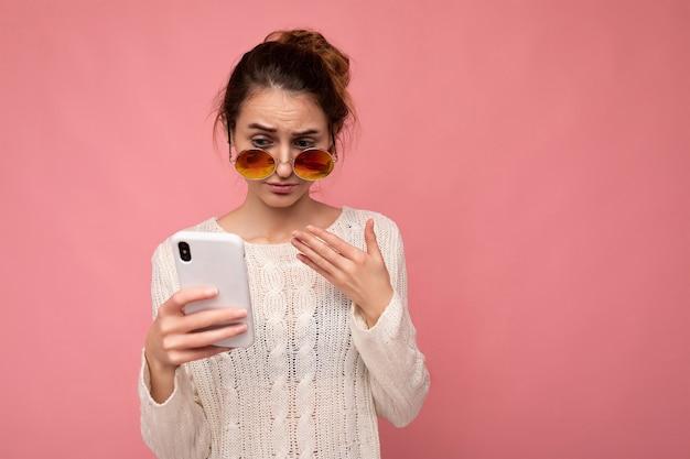 Foto einer attraktiven, unzufriedenen jungen frau, die eine lässige weiße bluse und eine bunte sonnenbrille trägt, die über einer rosa hintergrundwand isoliert ist und das telefon mit blick auf das gadjet-display verwendet Premium Fotos