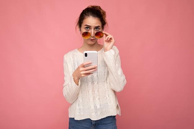 Foto einer attraktiven, verrückten überraschten jungen frau, die lässige, stilvolle kleidung trägt, die isoliert über dem hintergrund steht, mit kopienraum, der das mobiltelefon hält und in die kamera schaut.