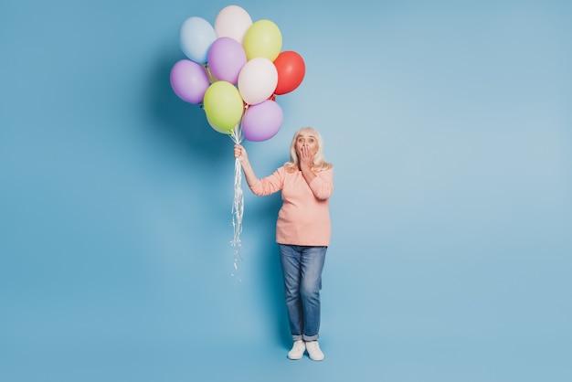 Foto einer charmanten alten frau, die luftballons in rosa pullover auf blauem hintergrund hält