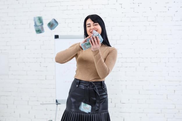 Foto einer charmanten frau mit einem lächeln, die geld in den händen hält und es in die luft wirft Premium Fotos