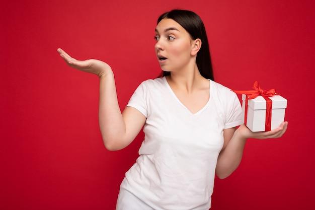 Foto einer charmanten, positiv überraschten jungen brünetten weiblichen person, die über einer roten hintergrundwand isoliert ist?