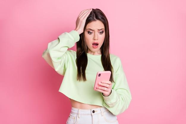 Foto einer charmanten schockierten dame, die den telefonarm auf dem kopf hält, schreckliche nachrichten lesen unfollower-blog-statistiken tragen lässige grüne erntepullover-jeansrock isoliert rosa pastellfarbenem hintergrund