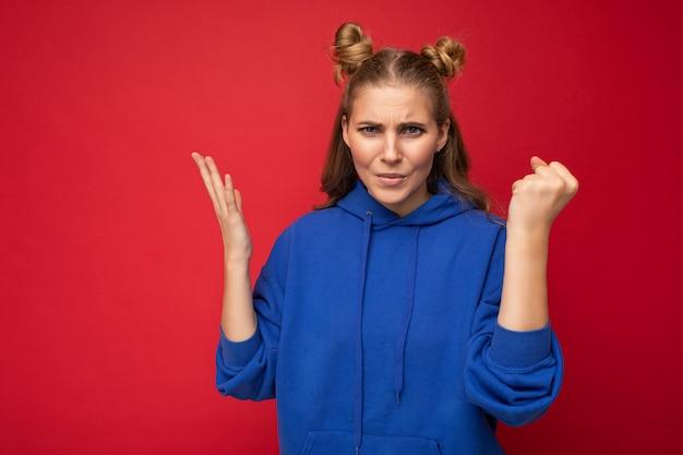 Foto einer emotional aggressiven jungen attraktiven blonden frau mit zwei hörnern mit aufrichtigen emotionen, die einen hellblauen hoodie einzeln auf rotem hintergrund mit freiem platz trägt und faust zeigt.