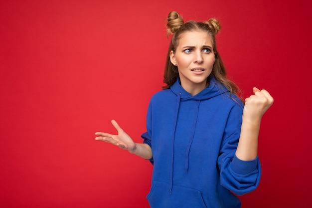 Foto einer emotional aggressiven jungen, schönen blonden frau mit zwei hörnern mit aufrichtigen emotionen, die den hellblauen hoodie des hipsters einzeln auf rotem hintergrund mit freiem raum trägt und faust zeigt.