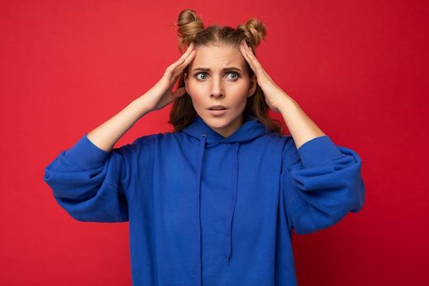 Foto einer emotional schockierten jungen hübschen blonden frau mit zwei hörnern mit aufrichtigen emotionen, die einen hellblauen hoodie des hipsters einzeln auf rotem hintergrund mit kopienraum trägt.