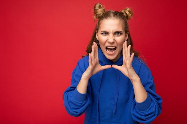 Foto einer emotional unzufriedenen jungen, schönen, blonden frau mit zwei hörnern mit aufrichtigen emotionen, die einen trendigen hellblauen hoodie einzeln auf rotem hintergrund mit leerem raum und schreien trägt.