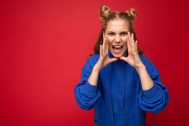 Foto einer emotional wütenden jungen, schönen, blonden frau mit zwei hörnern mit aufrichtigen emotionen, die einen trendigen, hellblauen hoodie trägt, einzeln auf rotem hintergrund mit leerem raum und schreien.
