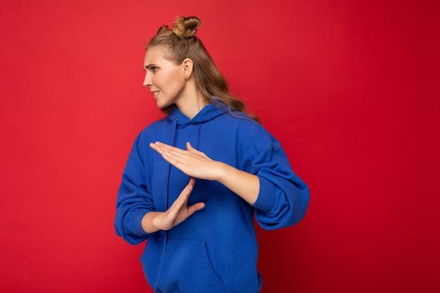 Foto einer emotionalen jungen attraktiven blonden frau mit zwei hörnern mit aufrichtigen emotionen, die einen hellblauen hipster-hoodie trägt, isoliert auf rotem hintergrund mit kopierraum und mit pausenzeichen