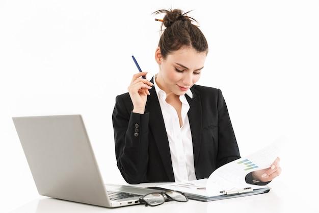 Foto einer erfolgreichen geschäftsfrau in formeller kleidung, die am schreibtisch sitzt und am laptop im büro arbeitet, isoliert über weißer wand