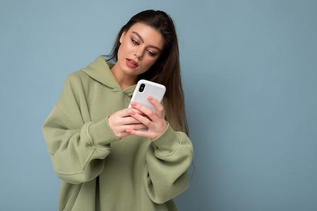 Foto einer ernsten schönen jungen brünetten frau, die einen stylischen grünen hoodie mit handy trägt