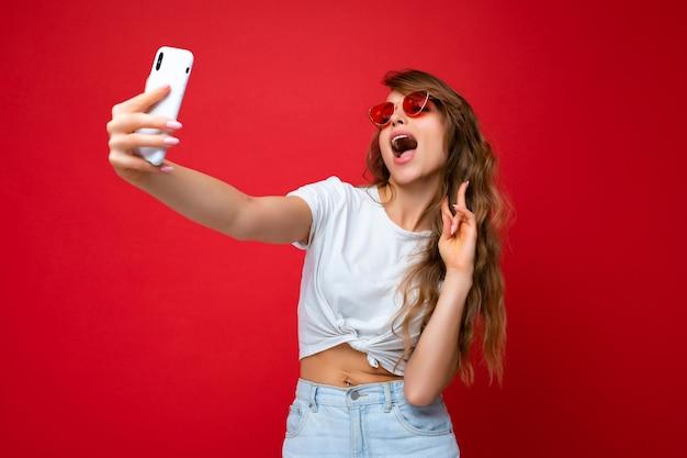 Foto einer erstaunlichen schönen jungen blonden frau, die ein handy hält und ein selfie-foto mit macht Premium Fotos