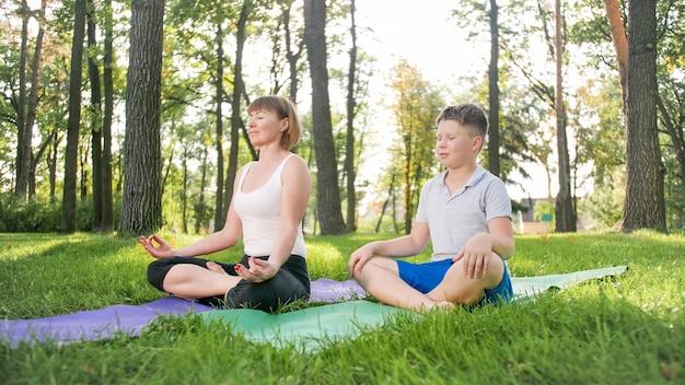 Foto einer frau mittleren alters, die ihren schüler im yoga-kurs im park unterrichtet. woamn mit teenager, der fitness, meditation und yoga auf gras im wald praktiziert