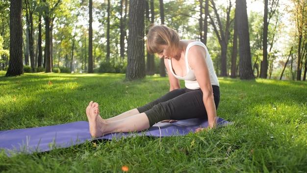 Foto einer frau mittleren alters in sportkleidung, die draußen im park yoga praktiziert. frau mittleren alters, die sich im wald ausdehnt und meditiert