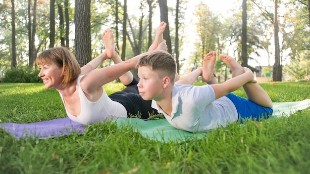 Foto einer frau mittleren alters mit einem 12-jährigen teenager, der yoga praktiziert und im park meditiert. familie entspannen und fitness in der natur machen