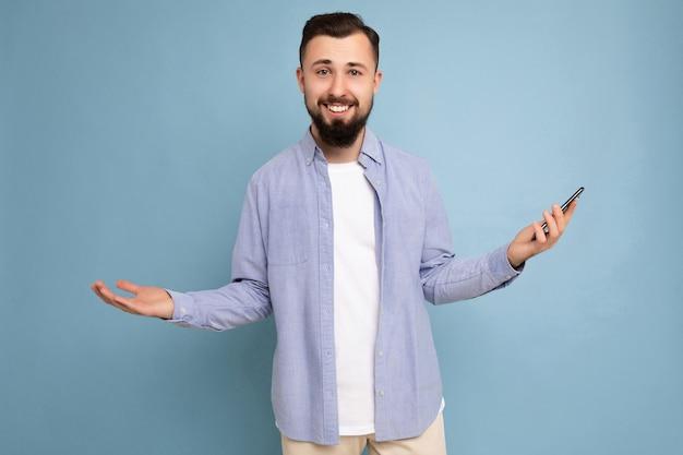 Foto einer fröhlich lächelnden, gutaussehenden jungen brünetten unrasierten männlichen person mit bart, die stylisch trägt