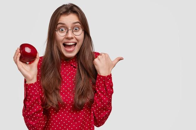 Foto einer fröhlichen dunkelhaarigen frau mit überglücklichem ausdruck, zeigt auf die rechte seite, trägt saftigen roten apfel