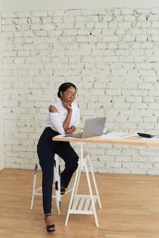 Foto einer fröhlichen, fröhlichen mischlingsfrau im weißen hemd, die training oder konferenz mit laptop hält.