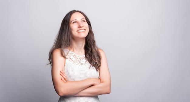 Foto einer fröhlichen jungen frau, die mit verschränkten armen lächelt und wegschaut