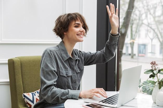 Foto einer fröhlichen jungen hübschen business-studentin, die im café drinnen sitzt und den laptop-computer verwendet, der freunden zuwinkt.