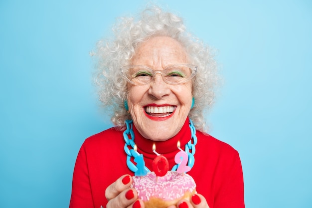 Foto einer fröhlichen, modischen älteren dame, die zahnig lächelt, hält süßen glasierten donut mit brennenden zahlenkerzen macht wunsch an ihrem geburtstag trägt roten pullover transapant brille posiert drinnen