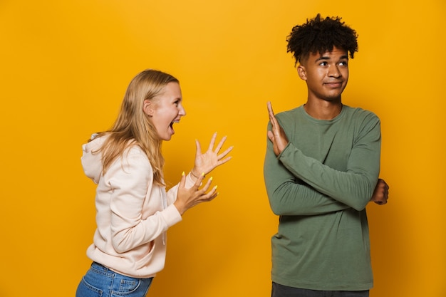 Foto einer gestressten frau 16-18, die einen jungen mann streitet und anschreit, isoliert auf gelbem hintergrund