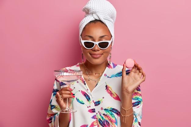 Foto einer glücklichen dunkelhäutigen frau schließt die augen und lächelt sanft genießt es, zeit zu hause zu verbringen, hält köstliche makronen und gläser martini-cocktail trägt morgenmantel isoliert über rosa wand