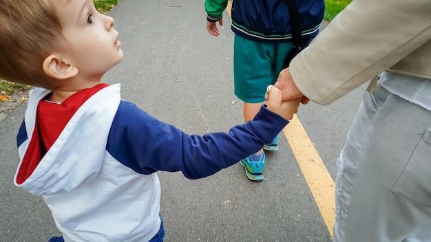 Foto einer glücklichen familie mit einem kleinen jungen, der an den händen hält und im park spazieren geht