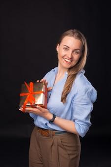 Foto einer glücklichen jungen frau, die eine rote geschenkbox auf schwarzem hintergrund hält