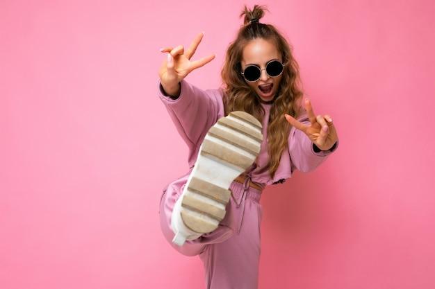 Foto einer glücklichen positiven jungen attraktiven blonden lockigen frau mit aufrichtigen emotionen, die trendige rosa sportbekleidung und sonnenbrillen einzeln auf rosafarbenem hintergrund mit kopienraum trägt und spaß hat.