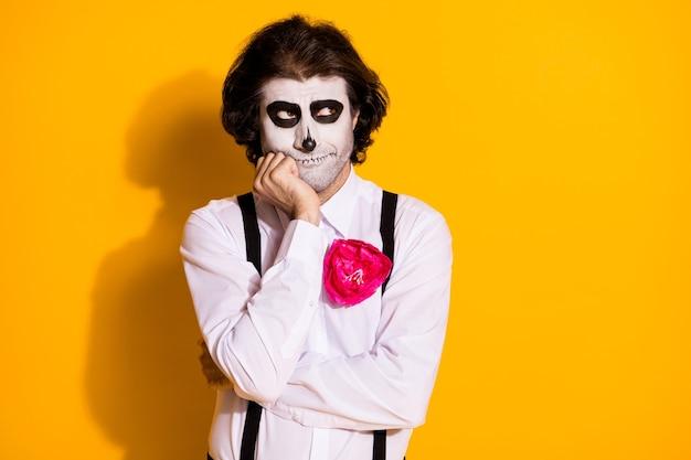 Foto einer gruseligen, nachdenklichen zombie-kreatur mit borsten, die hand wange sieht leer aus, warte oktober karneval tragen weißes hemd rose tod kostüm hosenträger isoliert gelber hintergrund
