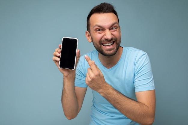 Foto einer gutaussehenden, verrückten, emotional lächelnden erwachsenen männlichen person, die gut aussieht und ein lässiges outfit trägt?