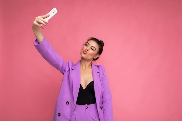 Foto einer hübschen jungen frau, die lila anzug trägt, der selfie-foto auf dem handy macht