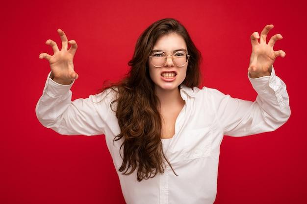 Foto einer jungen emotionalen attraktiven brunet-dame mit aufrichtigen emotionen, die ein lässiges weißes hemd trägt und