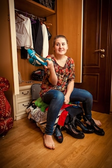 Foto einer jungen frau, die auf einem überfüllten koffer sitzt und schuh hält holding