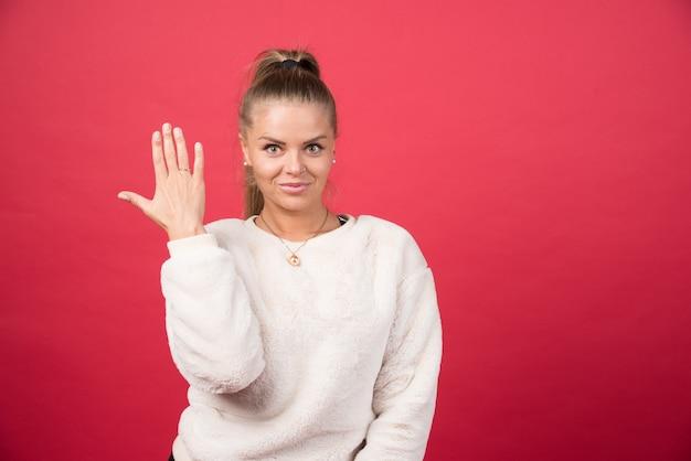 Foto einer jungen frau, die ihre hand oben zeigt
