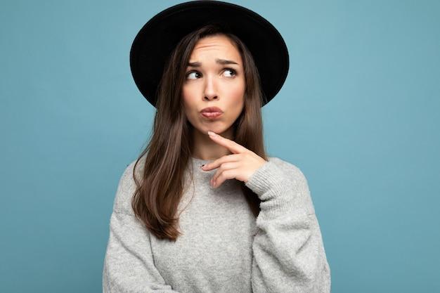 Foto einer jungen, nachdenklichen, attraktiven, hübschen brünetten frau mit aufrichtigen emotionen, die einen lässigen grauen pullover und einen schwarzen hut trägt, einzeln auf blauem hintergrund mit freiem raum und denken