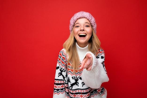 Foto einer jungen positiven entzückenden, glücklichen, schönen blonden frau mit aufrichtigen emotionen, die rosa strickmütze und winterpullover trägt, einzeln auf rotem hintergrund mit leerem raum und auf die kamera gerichtet